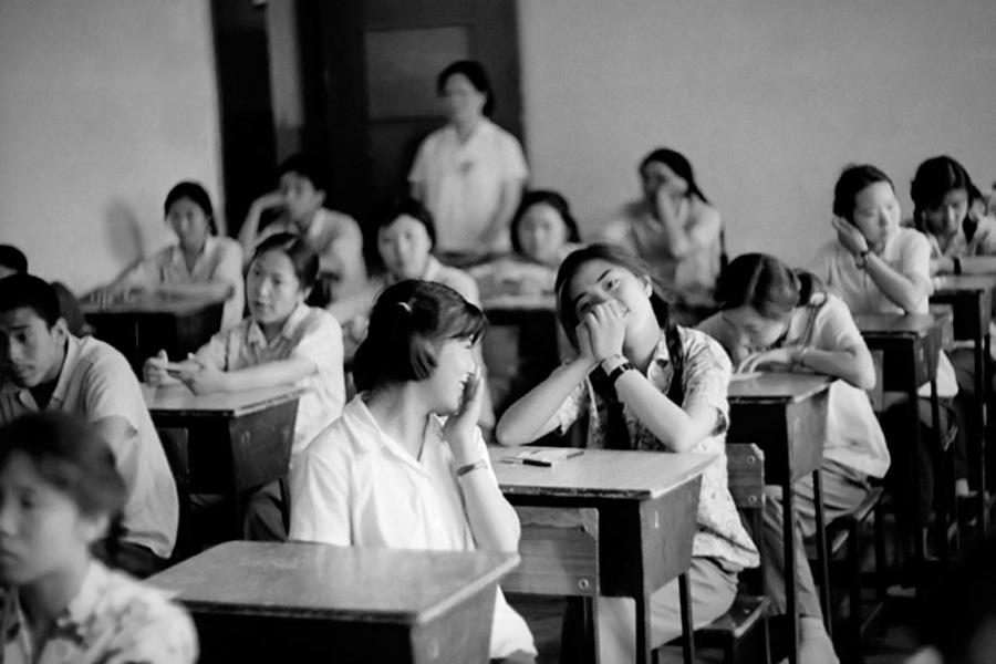 1980年,开考前两名女生在交谈。她们的笑容给沉闷的考场带来一丝轻松的气息。摄影/任曙林