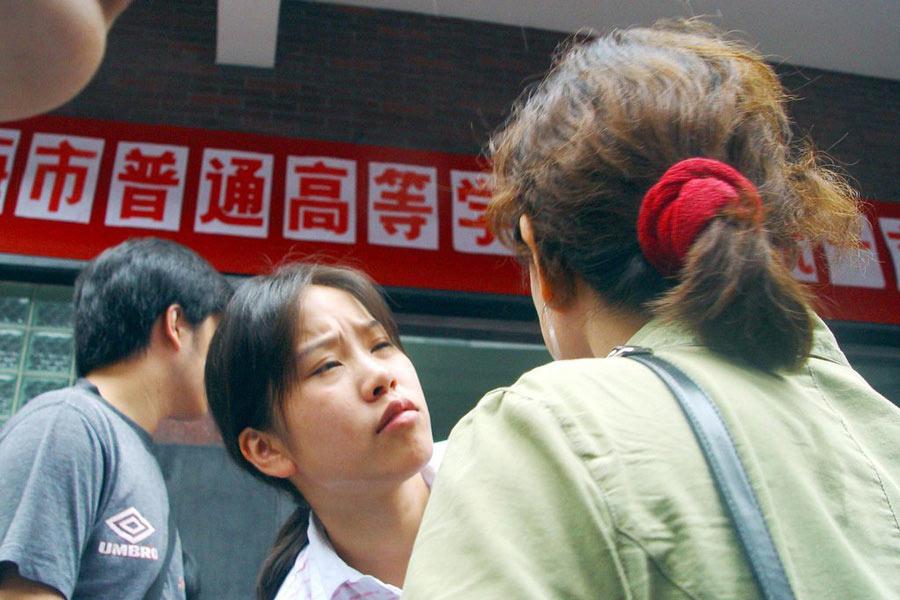 """2002年7月7日,上海市92800多名考生冒雨走进全市3800多个考场参加高考。而首场的语文考试作文""""面向大海"""",因取材范围过大,颇让部分考生感到无所适从,纷纷表示心里没底。图为一位女生刚出考场,便向母亲诉苦。"""