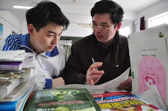 2011年3月14日,在课间,父亲王宝峰(右)与参加完美术专业课考试的儿子王旭东(左)相互交流学习体会。