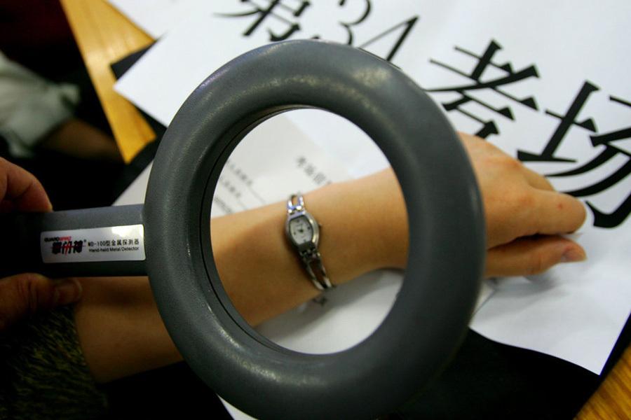 """2005年6月6日,河南省702个考点的7万名监考老师同时在各地进行考前考务培训。今年第一次在考场使用的""""金属探测器"""",杜绝手机等通讯工具进入考场。"""