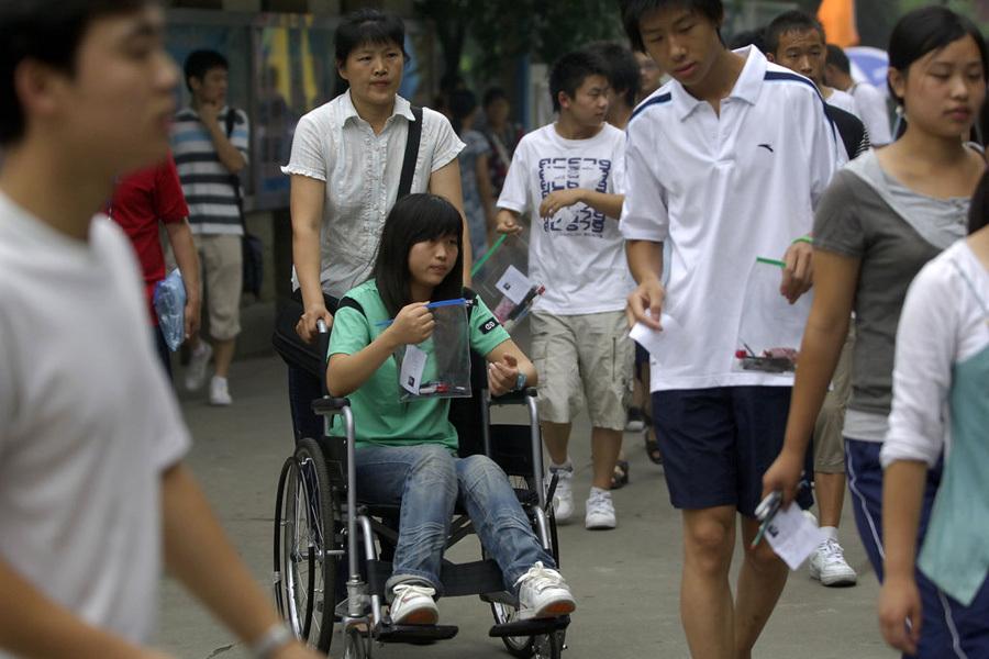 2008年7月3日,成都石室中學考點,一名在地震中腳部受傷的漩口中學考生坐在輪椅上進入考場。當日,四川省40個縣(市)區的96421名考生在77個考點、3274間考室參加延期高考。